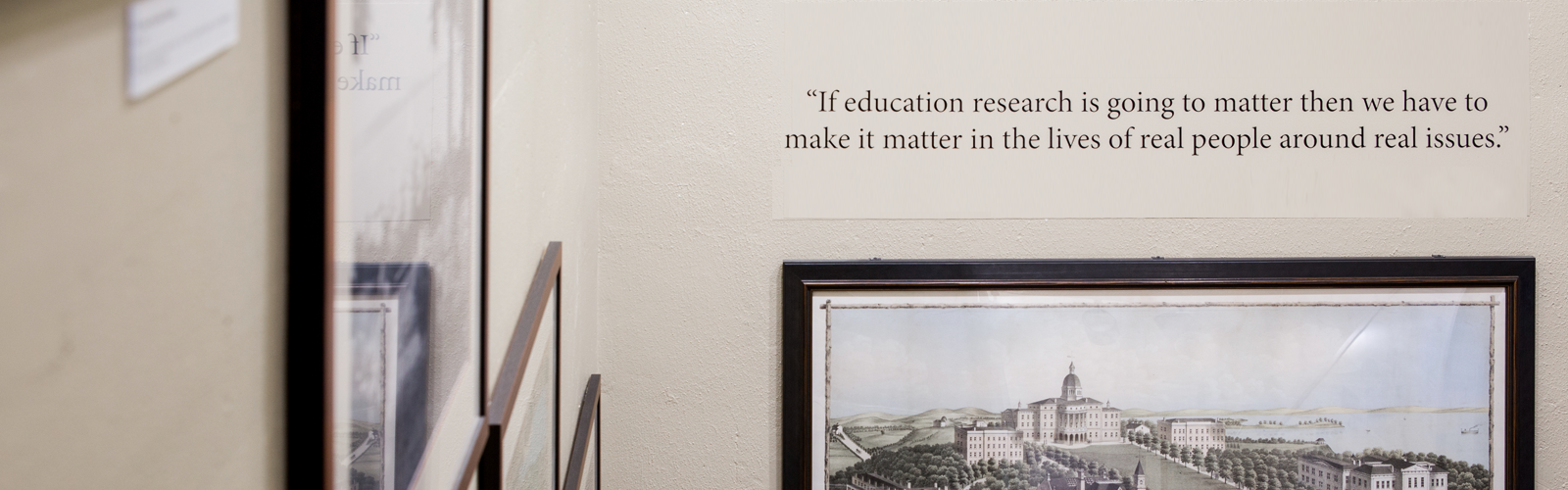 Education quote in a stairwell with illustration of campus